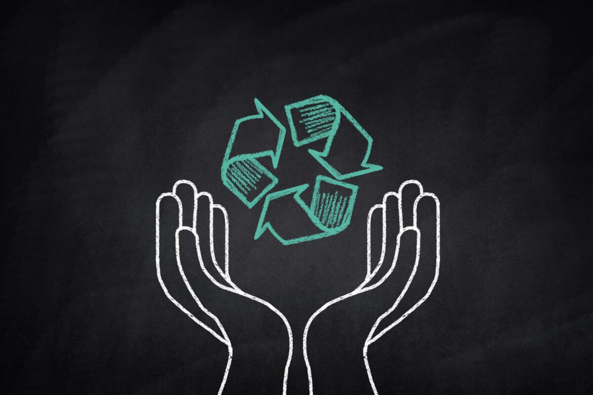 hands-holding-a-recycling-symbol-on-a-blackboard-min