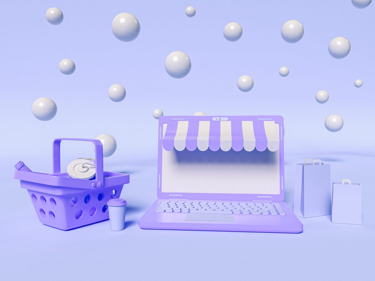 3d-illustration-a-laptop-with-a-shopping-basket-and-paper-bags-online-shopping-and-e-commerce-concept-min