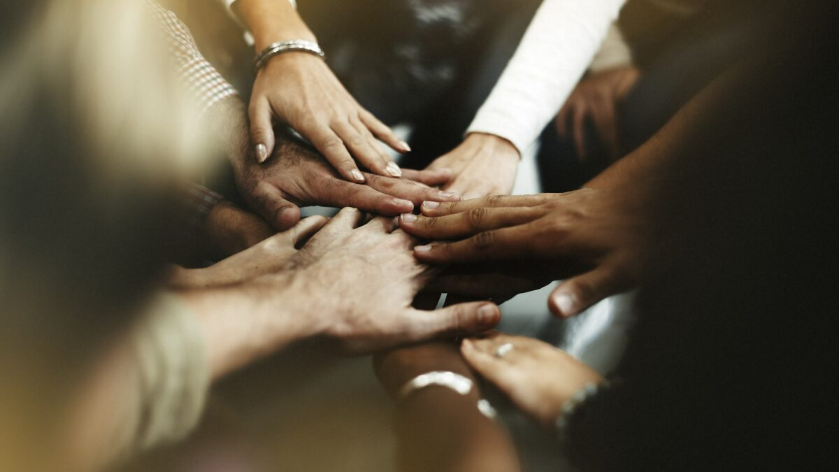 closeup-diverse-people-joining-their-hands-min