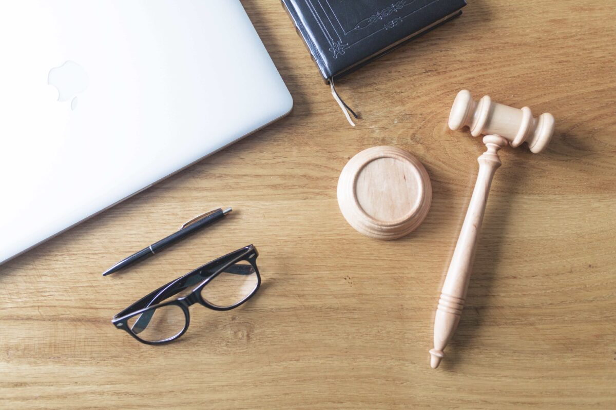 high-angle-view-laptop-spectacles-gavel-pen-wooden-background-wooden-desk-min