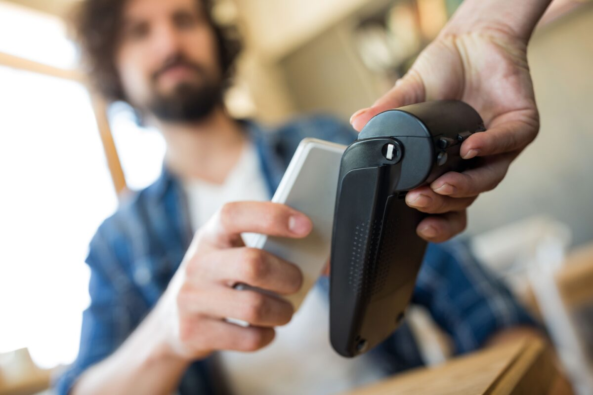 man-paying-with-nfc-technology-on-mobile-phone-min