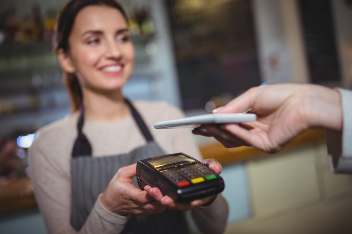 woman-paying-bill-through-smartphone-using-nfc-technology-min