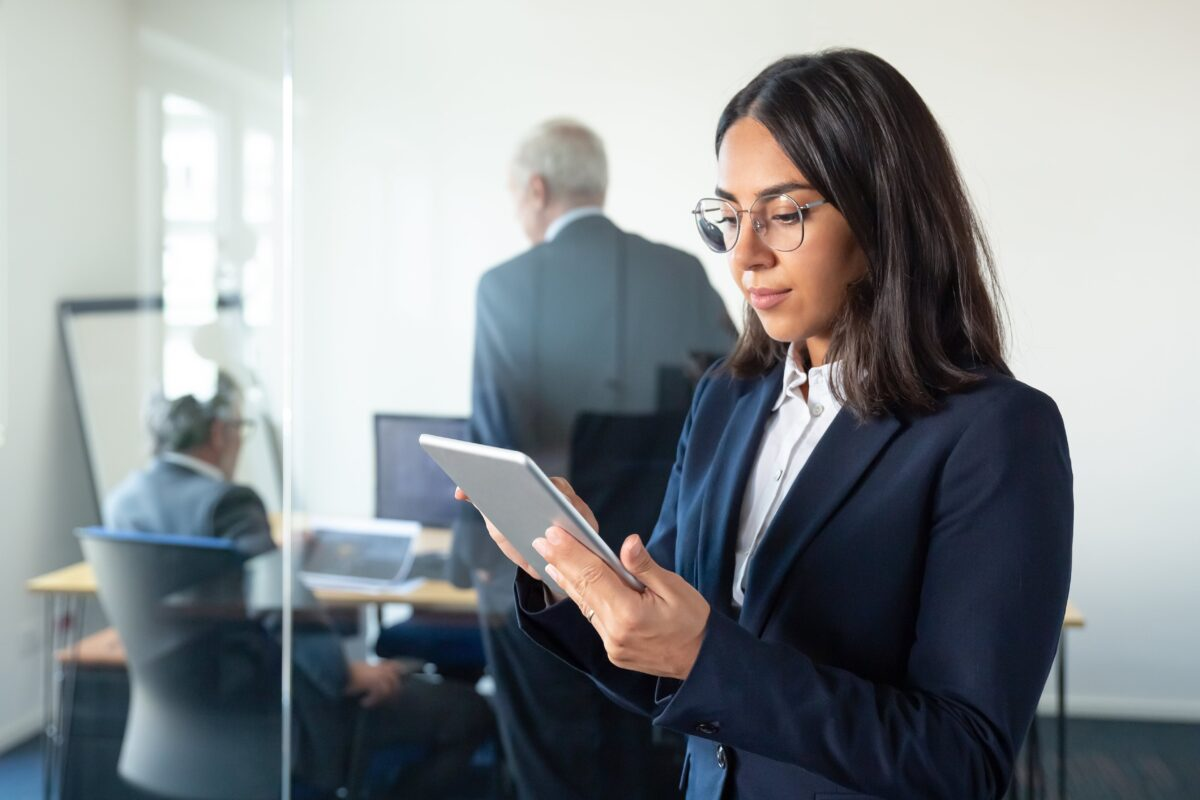focused-office-lady-in-glasses-using-tablet-while-two-mature-businessmen-discussing-work-behind-glass-wall-copy-space-communication-concept-min