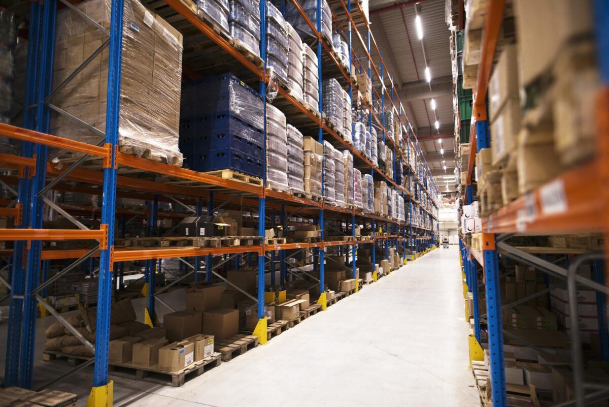 interior-of-large-distribution-warehouse-with-shelves-stacked-with-palettes-and-goods-ready-for-the-market-min