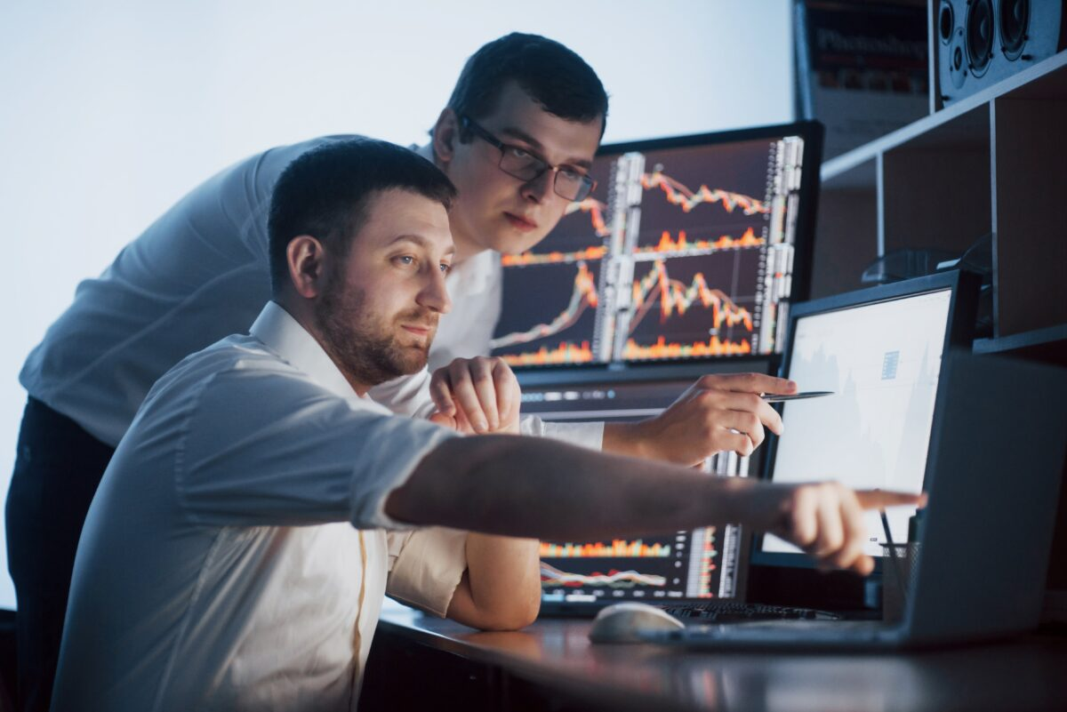 team-stockbrokers-are-having-conversation-dark-office-with-display-screens-analyzing-data-graphs-reports-investment-purposes-creative-teamwork-traders-min