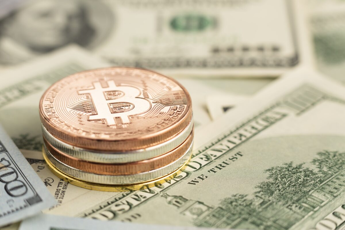 close-up-bitcoin-pile-on-top-of-banknotes-min