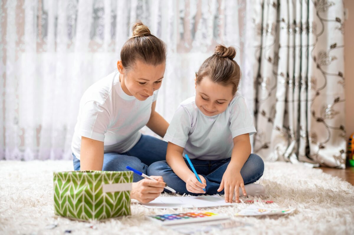 mom-and-her-daughter-are-playing-together-at-home-on-the-floor-happy-and-smiling-min