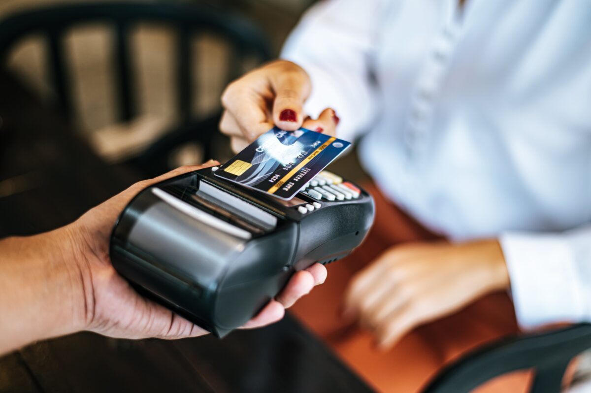 close-up-image-woman-paying-with-credit-card-cafe-min