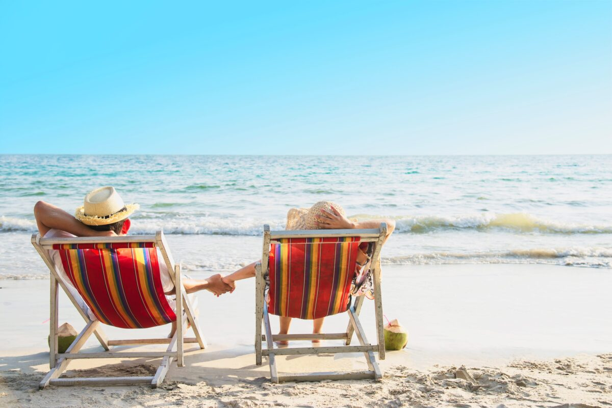 relax-couple-lay-down-on-beach-chiar-with-sea-wave-man-and-woman-have-vacation-at-sea-nature-concept-min