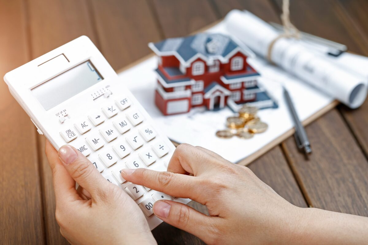 a-female-hand-operating-a-calculator-in-front-of-a-villa-house-model-min