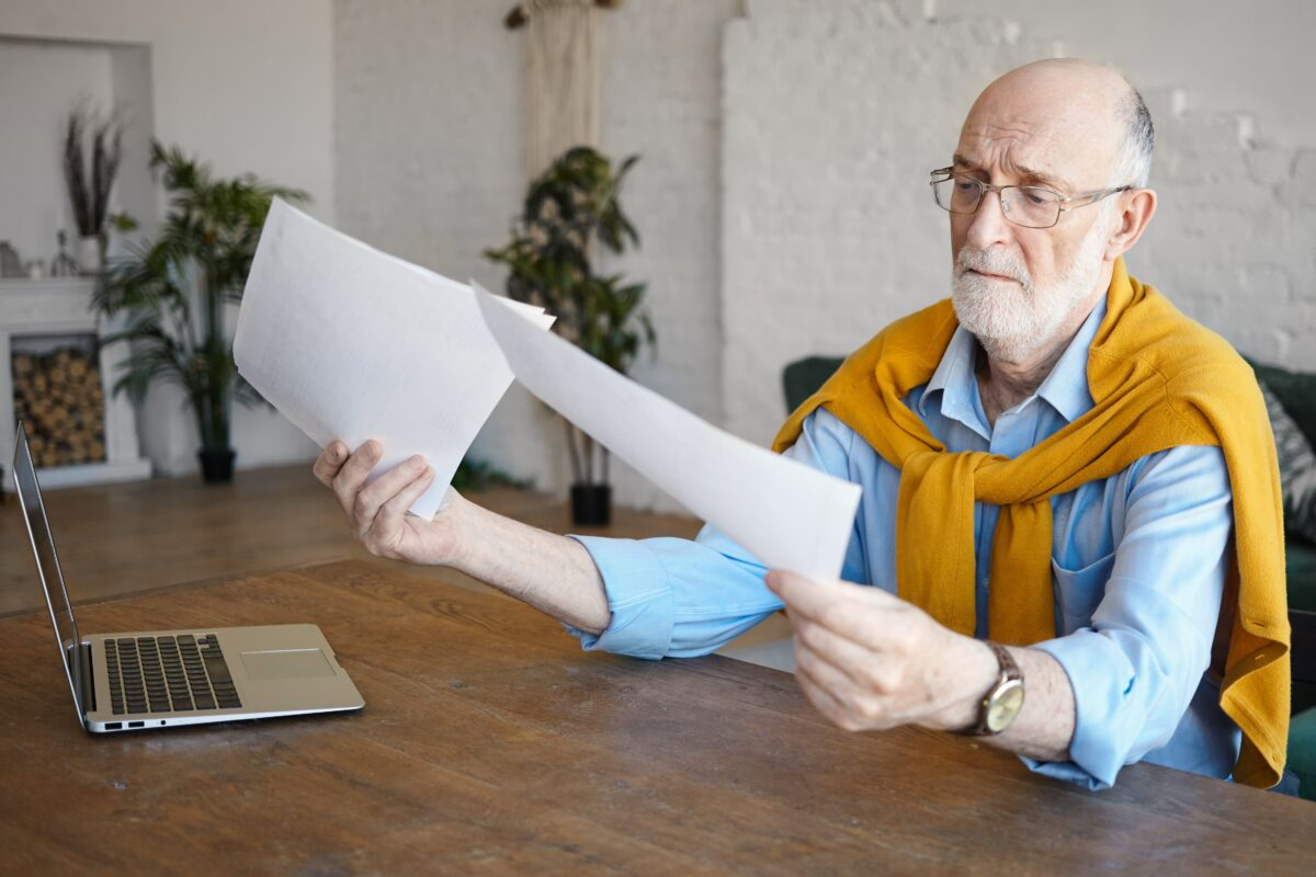 attractive-experienced-sixty-year-old-man-accountant-holding-papers-having-concentrated-focused-look-while-working-on-financial-report-sitting-at-desk-using-laptop-people-lifestyle-and-technology-min