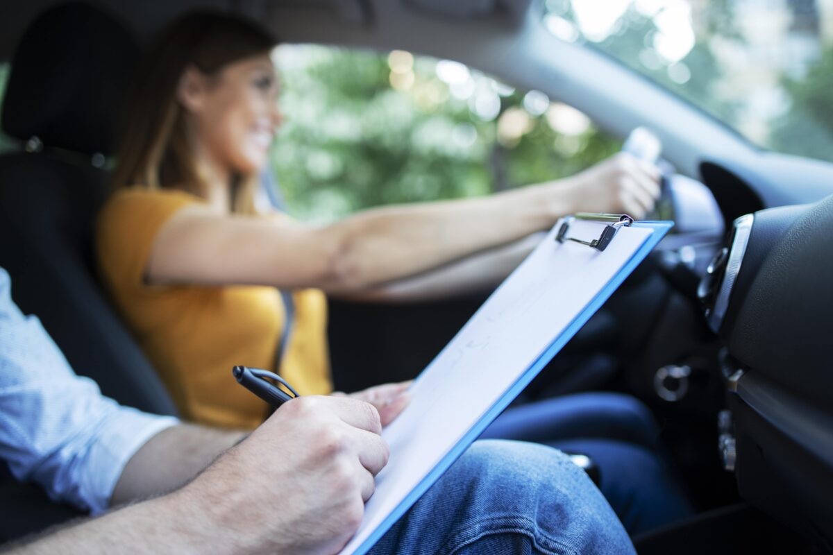 close-up-view-of-driving-instructor-holding-checklist-while-in-background-female-student-steering-and-driving-car-min-min