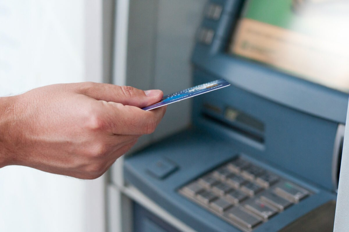 hand-inserting-atm-card-into-bank-machine-to-withdraw-money-businessman-men-hand-puts-credit-card-into-atm
