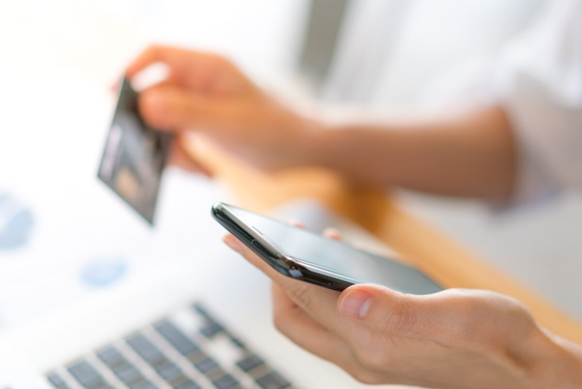 hands-holding-a-credit-card-using-laptop-computer-and-mobile-phone-for-online-shopping-min