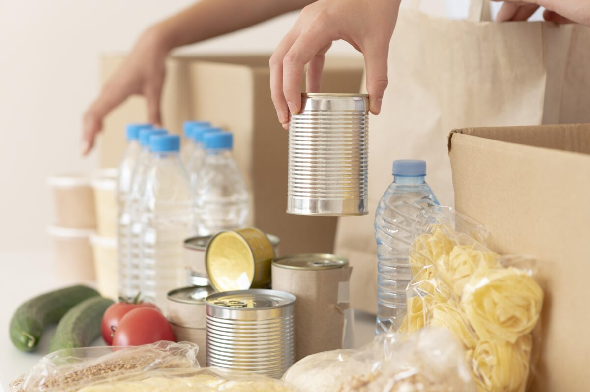 volunteers-putting-canned-food-for-donation-in-box