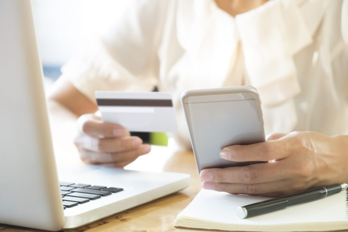 woman-holding-mobile-phone-and-credit-card-on-laptop-for-online-shopping-min