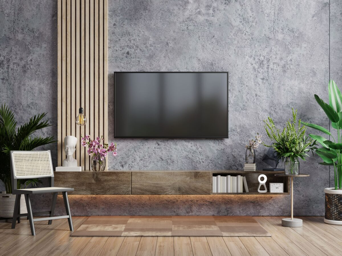 a-tv-in-modern-living-room-with-armchair-and-plant-on-concrete-wall-background-3d-rendering-min