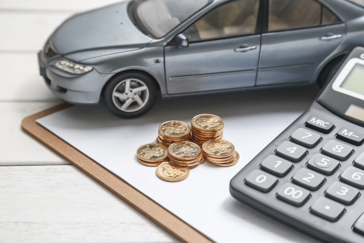 car-model-calculator-and-coins-on-white-table-min