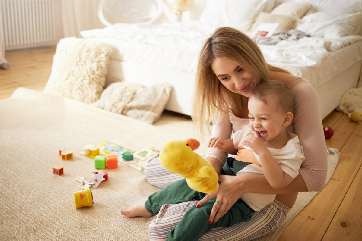 pretty-sister-spending-time-with-her-baby-brother-sitting-on-floor-in-bedroom-beautiful-young-babysitter-playing-with-little-boy-indoors-holding-stuffed-toy-duck-infancy-childcare-and-motherhood