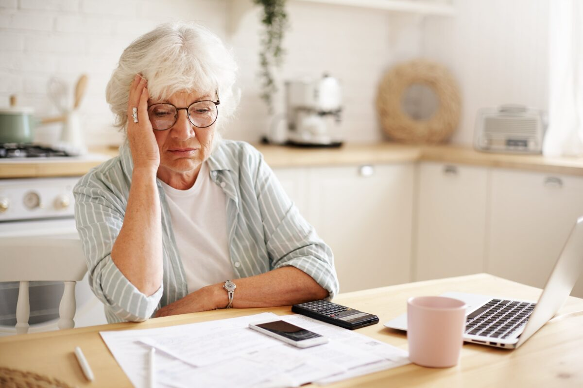 sad-frustrated-senior-woman-pensioner-having-depressed-look-holding-hand-on-her-face-calculating-family-budget-sitting-at-kitchen-counter-with-laptop-papers-coffee-calculator-and-cell-phone-min