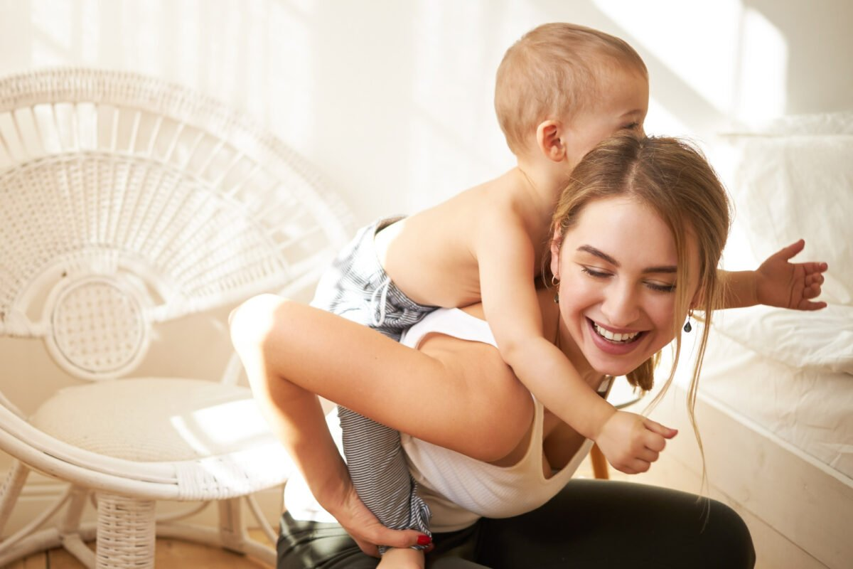 smiling-adorable-teenage-girl-babysitting-little-boy-giving-him-piggyback-ride-at-home-joyful-young-mother-riding-her-sweet-baby-son-on-back-enjoying-nice-time-together-indoors-having-fun