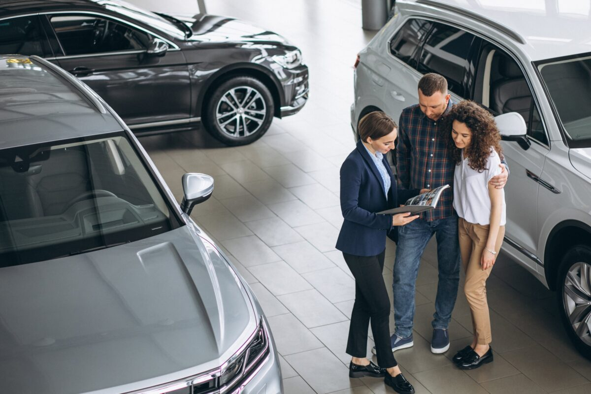 young-couple-talking-to-a-sales-person-in-a-car-showroom-min