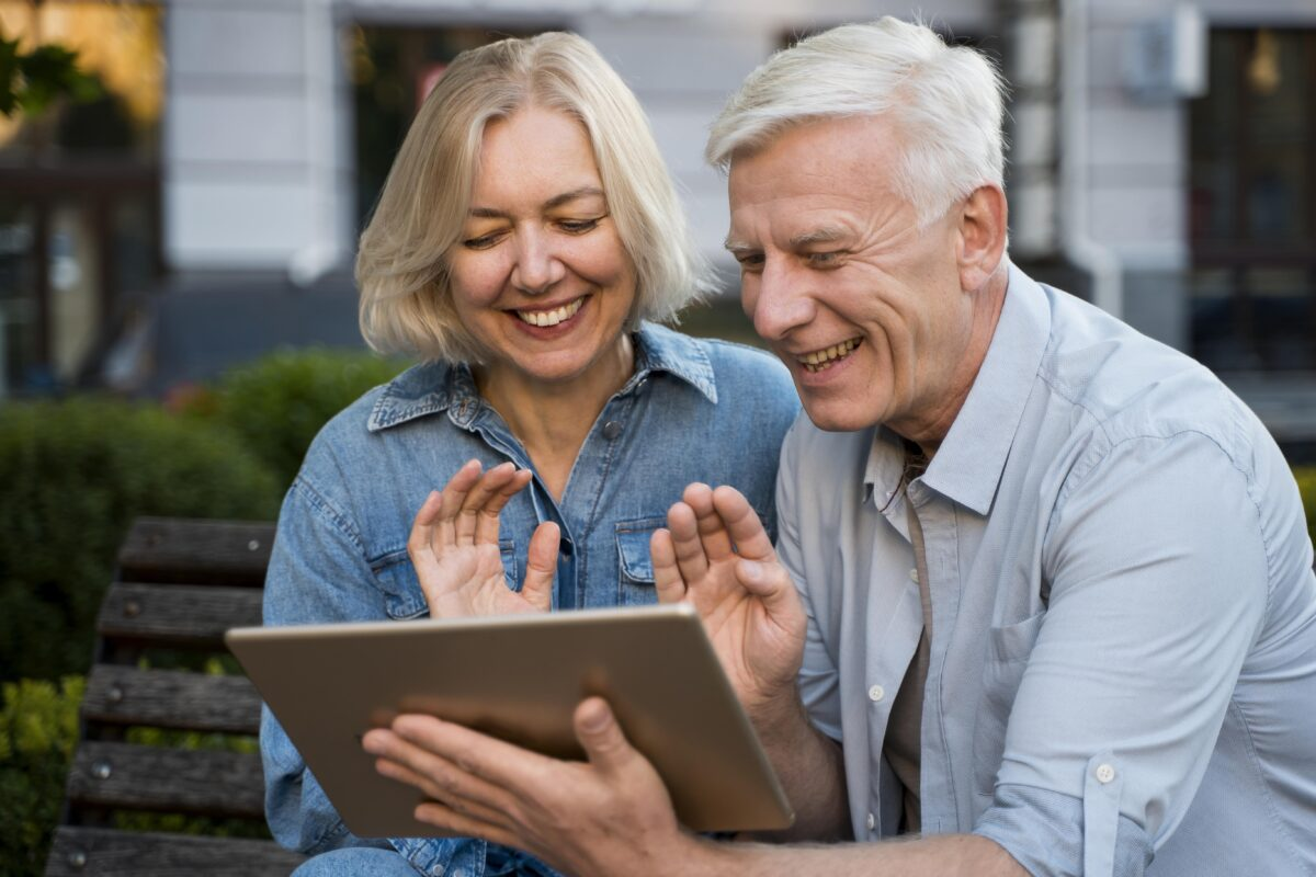 smiley-older-couple-waving-at-someone-they-re-talking-to-on-tablet