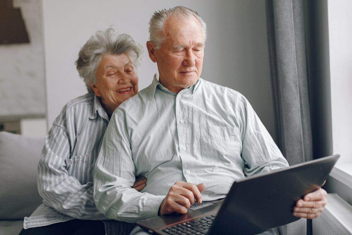 elegant-old-couple-sitting-at-home-and-using-a-laptop-min